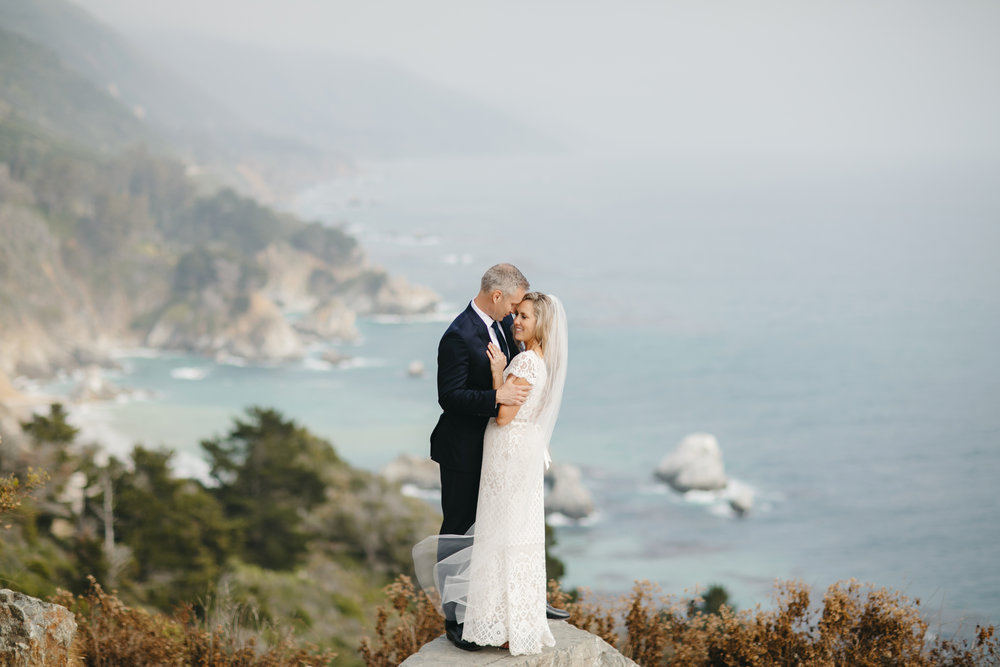 An adventurous couple embraces on the California Coast with Big Sur Destination Elopement Photographers Colby and Jess.