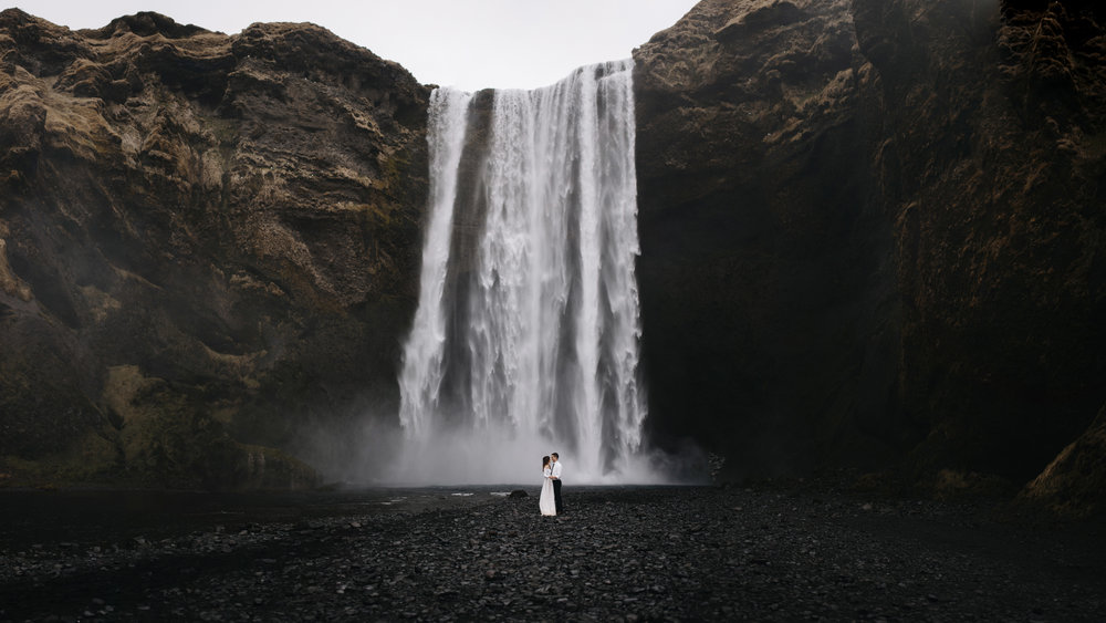 A couple holds each other in front of Skogafoss Waterfall during their Iceland Destination Elopement