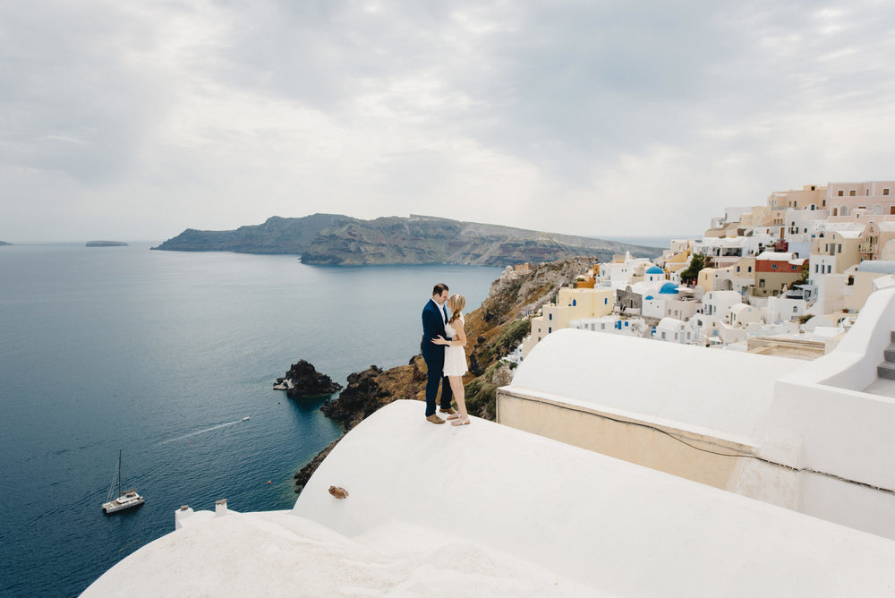 A bride and groom hug on a rooftop overlooking the Caldera during their Santorini Destination Elopement with Photographers Colby and Jess