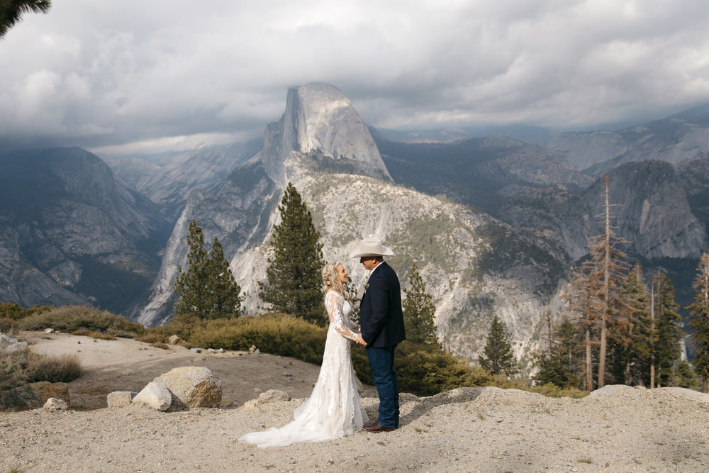 A couple elopes in front of half dome at glacier point with Yosemite Destination Elopement Photographers Colby and Jess.