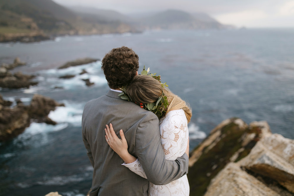 A couple shares a romantic moment watching waves crash during their Big Sur Destination Elopement with photographers Colby and Jess