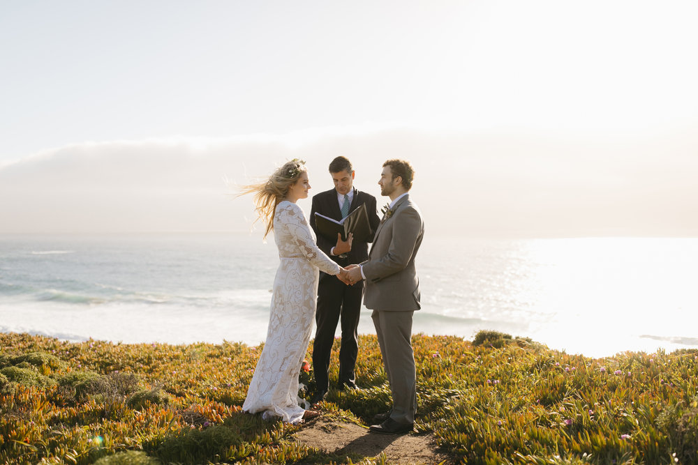 A beautiful bride and groom say their vows during sunset with Big Sur Destination Elopement Photographers Colby and Jess.