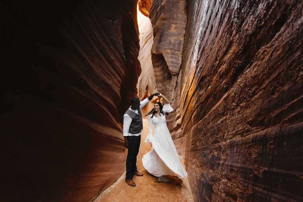 A man and woman dance in a slot canyon during their Antelope Canyon couples adventure photography session with Utah Destination Elopement Photographer Colby and Jess