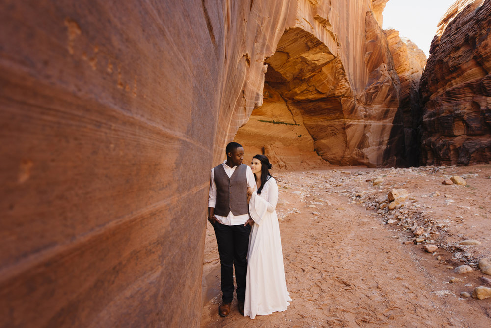 A couple embraces beside the red rock of Antelope Canyon during their Adventure couples photography session by Utah Destination Elopement Photographers Colby and Jess