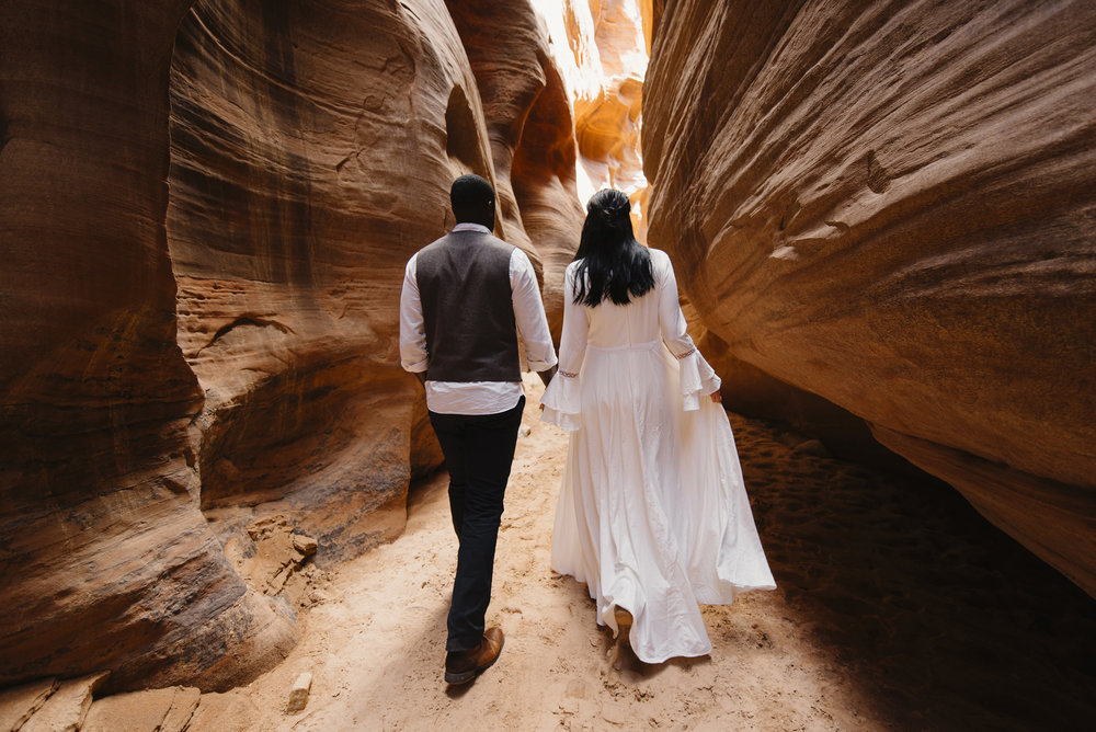 A couple walks holding hands through a slot canyon during their Antelope Canyon Adventure Engagement Photography Session by Utah Destination Elopement Photographer Colby and Jess