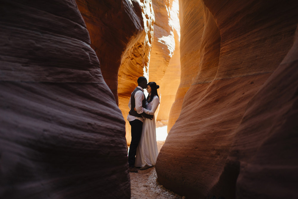 A couple embraces in a slot canyon during their Antelope Canyon Adventure Engagement Photography Session by Utah Destination Elopement Photographer Colby and Jess