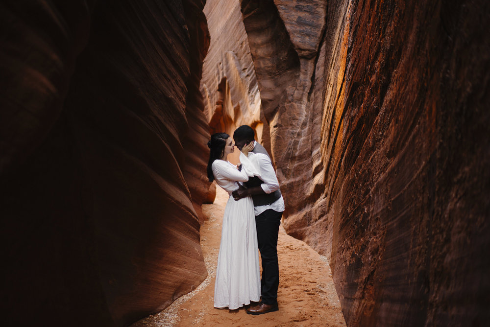 A couple embraces during their slot canyon adventure engagement photography session by Utah Destination Elopement Photographer Colby and Jess