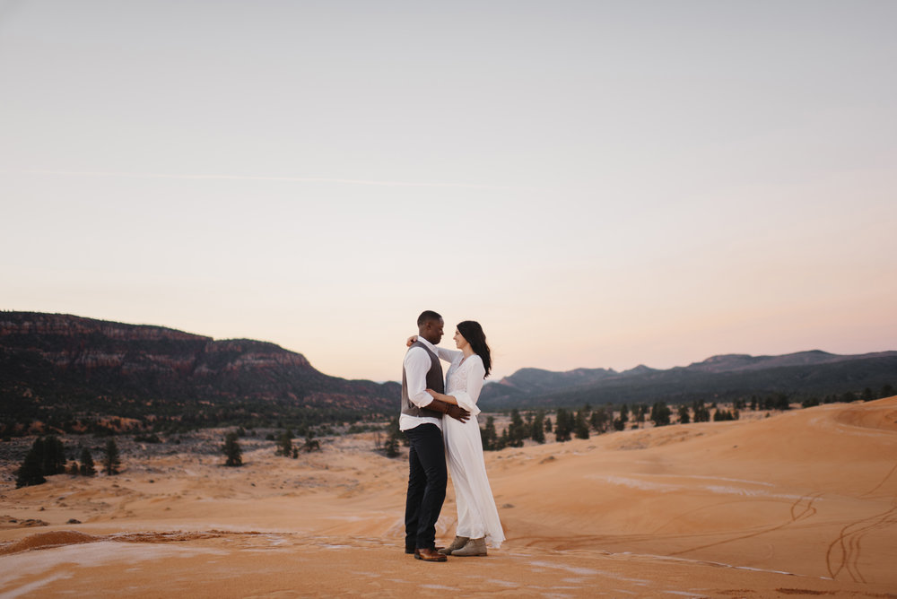 A couple shares a dance at pink coral sand dunes during their adventure couples photography session by Utah Destination Elopement Photographer Colby and Jess