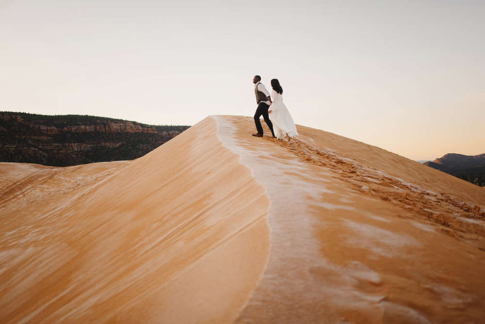 A couple climbs a sand dune during their Coral Pink Sand Dunes Engagement Photography Session with Utah Destination Elopement Photographer Colby and Jess