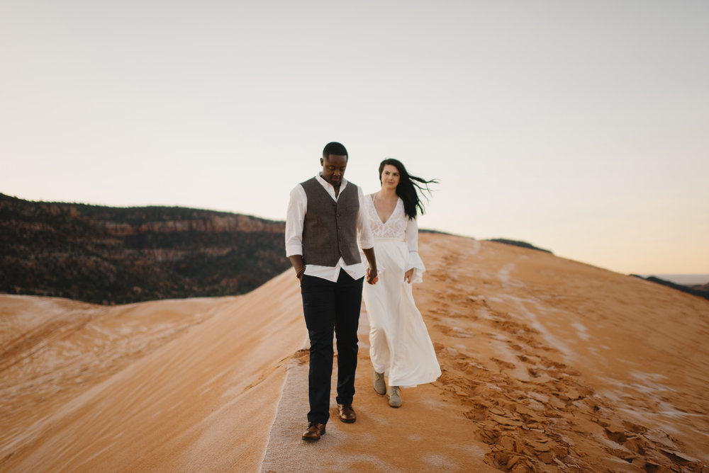 A man and woman hold hands exploring during their Coral Pink Sand Dunes Engagement Photography Session with Utah Destination Elopement Photographer Colby and Jess