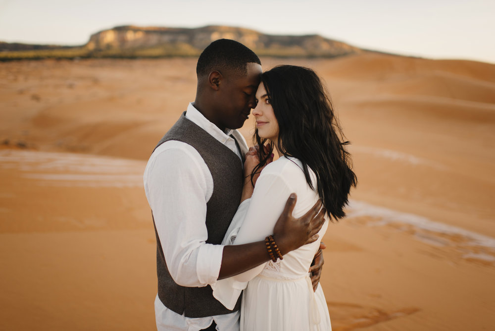 A man embraces his wife during their Anniversary Couples Adventure Photography Session with Utah Sand Dunes Destination Elopement Photographer Colby and Jess