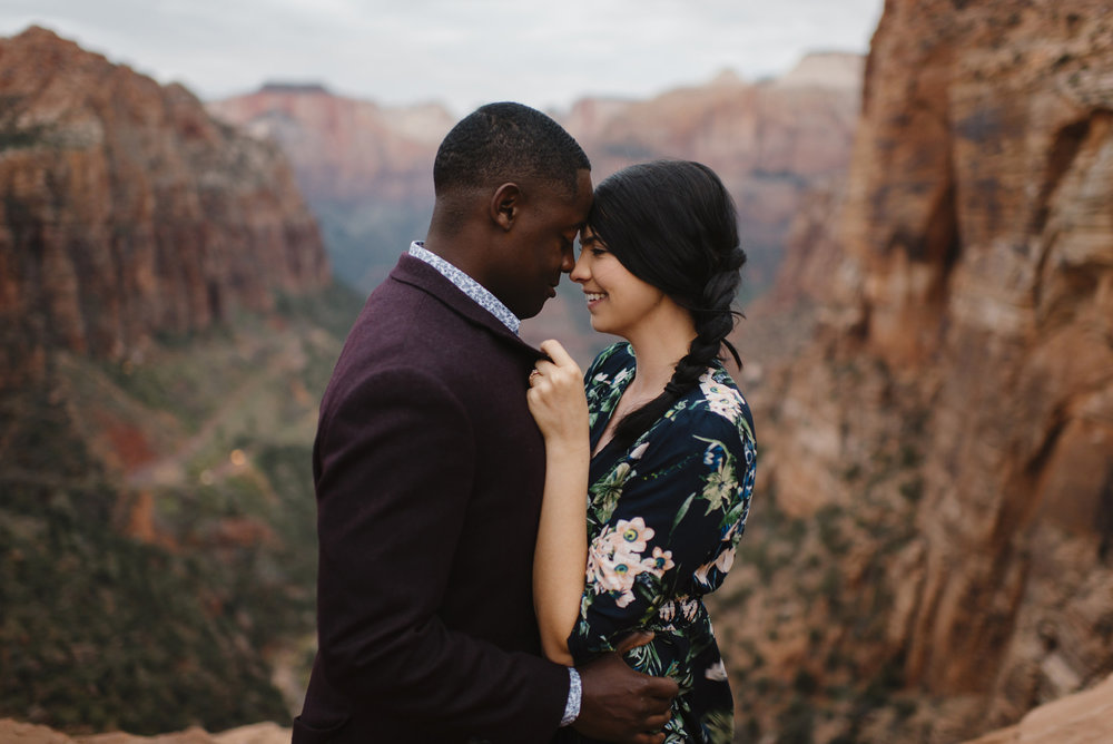 A man and woman snuggle close during their Angels Landing Adventure Engagement Photography Session with Zion National Park Elopement Photographer Colby and Jess