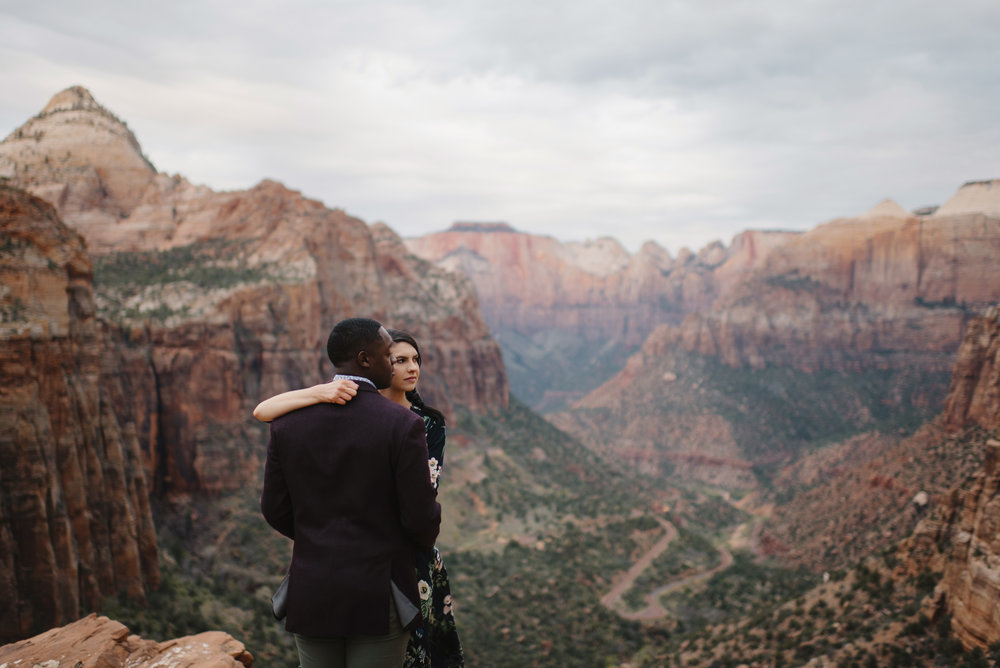 A man and woman look out from Angels Landing during their Zion Engagement Photography Session by Zion National Park Elopement Photographer Colby and Jess