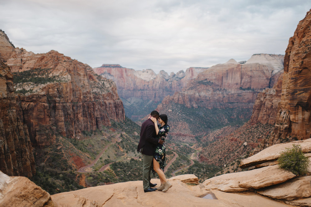 A couple hug each other during their Angels Landing Zion Engagement Photography Session by Zion National Park Elopement Photographer Colby and Jess