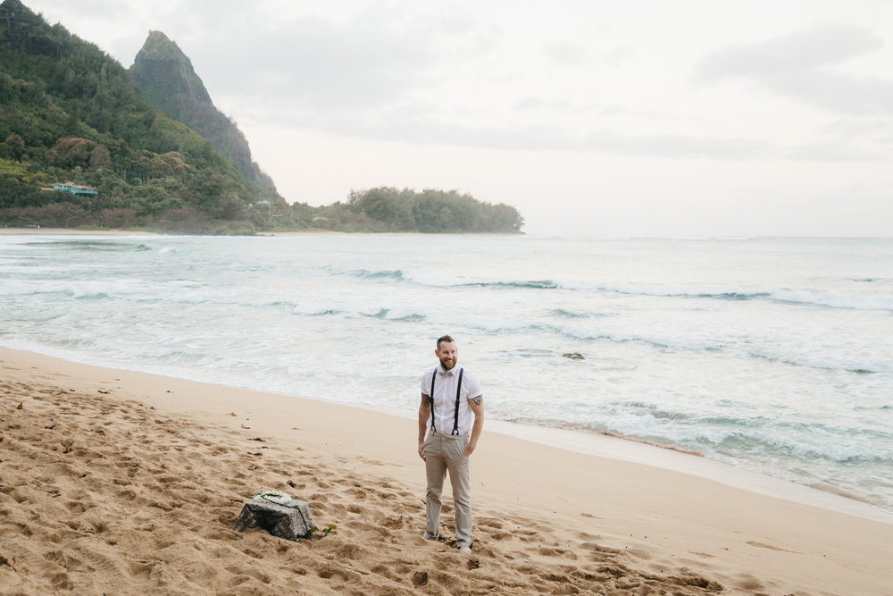 A groom waits for his bride on Tunnels Beach Kauai during adventure elopement by photographer Colby and Jess