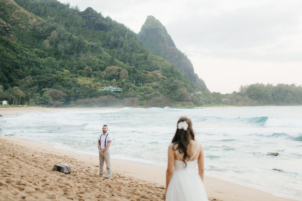 Groom sees in bride for first time during Tunnels Beach Elopement by Hawaii Wedding Photographers Colby and Jess