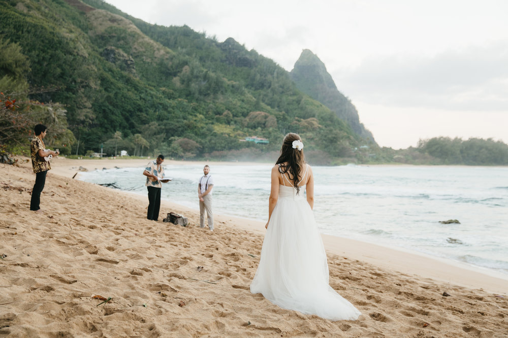 Bride walks across Tunnels Beach to her groom during Kauai Elopement photography by Hawaii Wedding Photographers Colby and Jess