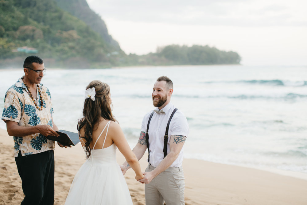 Bride and groom exchange vows during Tunnels Beach wedding ceremony with Kauai Elopement Photographers Colby and Jess