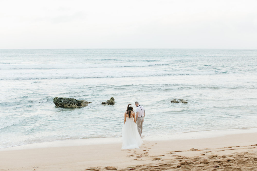 A couple walks on the beach after Tunnels Beach Elopement Ceremony by Kauai Wedding Photographers Colby and Jess