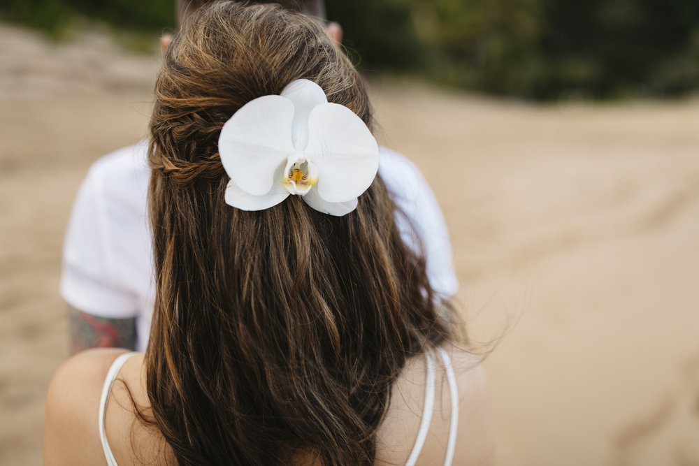 A bride's hair adorned with an orchid flower during her Tunnels beach wedding ceremony with Kauai Elopement Photographers Colby and Jess