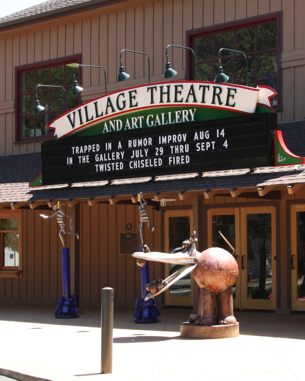 "Village Theatre signage was designed to evoke the historic past of the original building - a grange hall and one of the earliest buildings in Danville.   The interior redesign of the lobby lowered the finish floor level and facilitated removing exterior handicap ramps and allowing the Lobby/Art Gallery to flow outdoors onto a new ""sculpture"" plaza.  Design of the new historic-looking marquee involved a public review process. This project was a collaboration with Kirk E. Peterson and Associates."