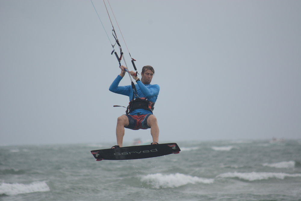 David Rogers catching some air on his kiteboarding in a pair of Patagonia board shorts.
