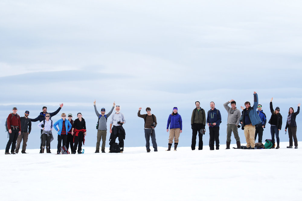 Scientists and research support staff wave from the top of the glacier at Palmer Station.