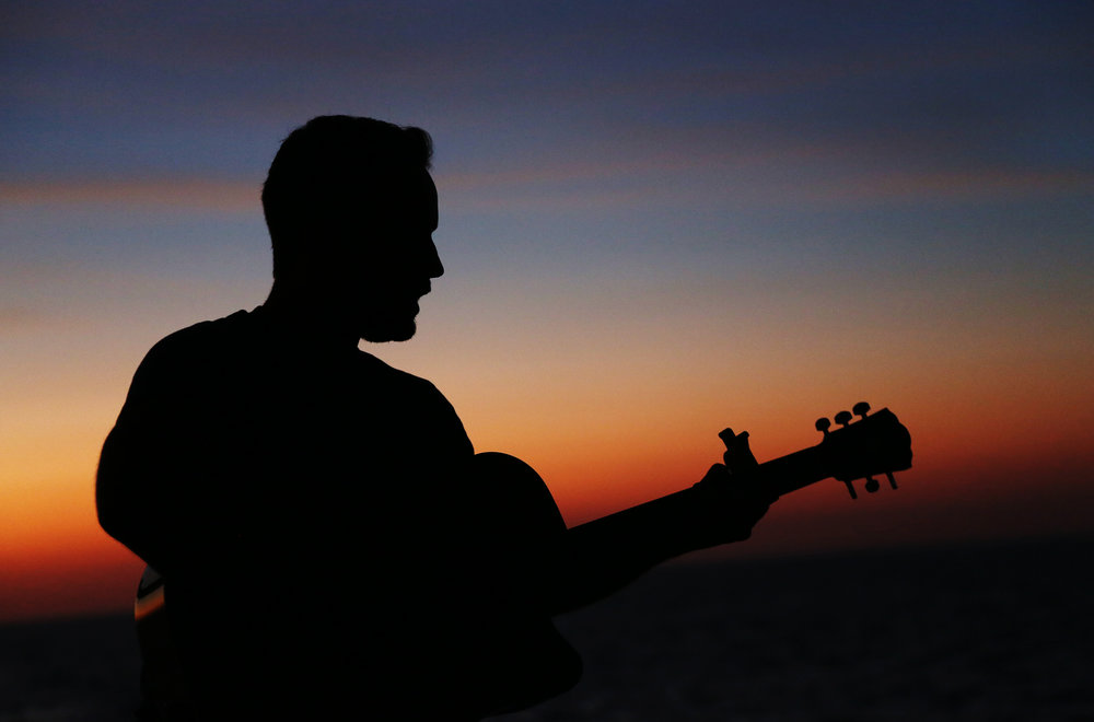 Luke MacNutt serenading his fellow crew members as the final light of the day fades behind him.