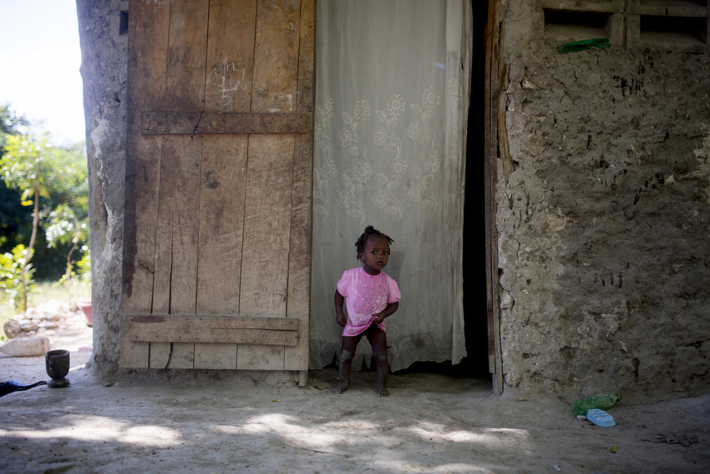 Estime Miradieu's youngest daughter Miloutchina stands in the doorway of his home. Miradieu has an income of a few hundred dollars per year, which is not enough to send all of his children to school.