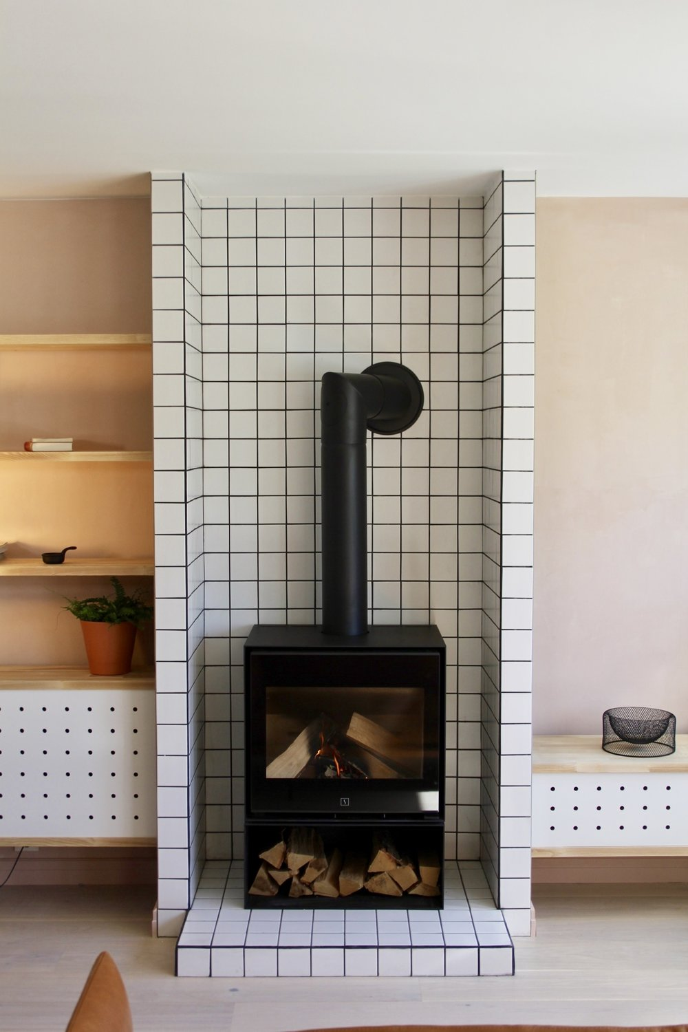 A fireplace was installed surrounded with white tiles, the same as in the kitchen,  to protect the surrounding shelves and furniture.
