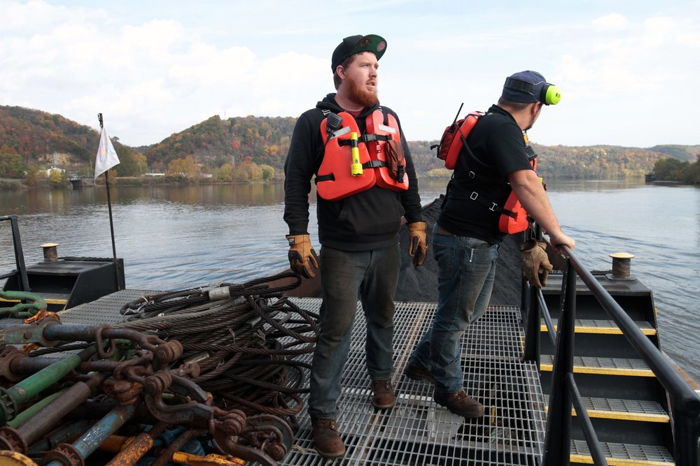 Deckhand Dustin Frazee (center) and lead deckhand Jeremy Groves look out over the Ohio River as their towboat, the D.L. Johnson, pushes a coal barge. Photo: Ryan Loew