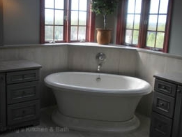 Bathroom design with a gray color scheme and freestanding tub.