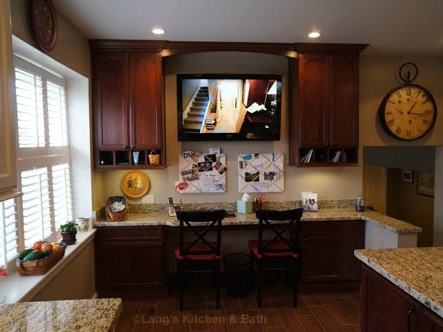 Kitchen design with integrated desk and flat screen television.