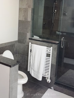 Bathroom design with radiator style towel warmer next to the shower for easy access to warm towels.