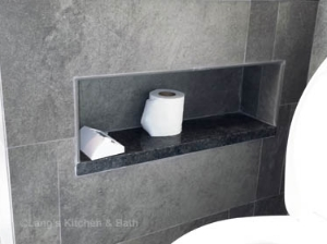Unique niche built in next to the toilet as an alternative to the traditional toilet roll holder.