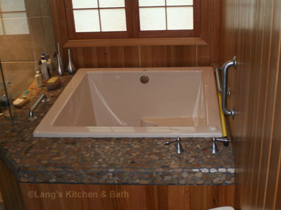Bathroom design with extra deep feature tub surrounded by river rocks and warm cedar wood.
