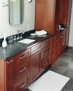Transitional style bathroom design in Yardley, PA featuring a dark wood vanity with customized storage.
