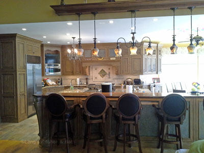 Kitchen design in New Hope, PA with distressed grey cabinets and island offset by a stylish lighting design.