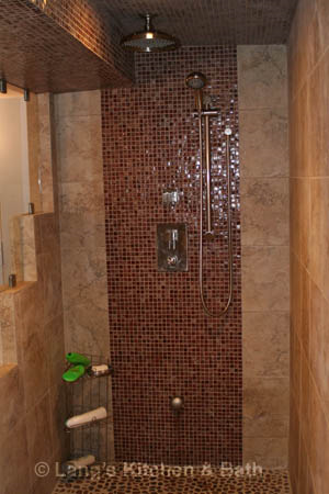 Bathroom design with a shower with mosaic tile feature wall and pebble floor.