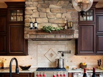 Traditional kitchen design with a stunning stone hood creating a focal point.