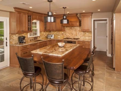 Traditional kitchen design featuring metal island lights and stools