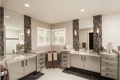 Contemporary bathroom design featuring gray vanity cabinets and gray and white tile design.