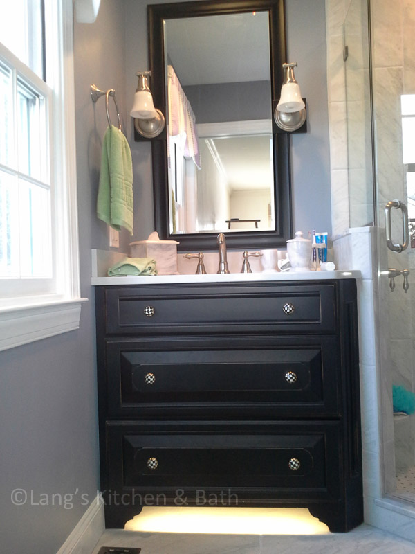 Traditional bathroom design with gray walls and a black wood vanity.