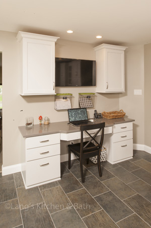 Kitchen design with built in desk and wall-mounted flat screen television.