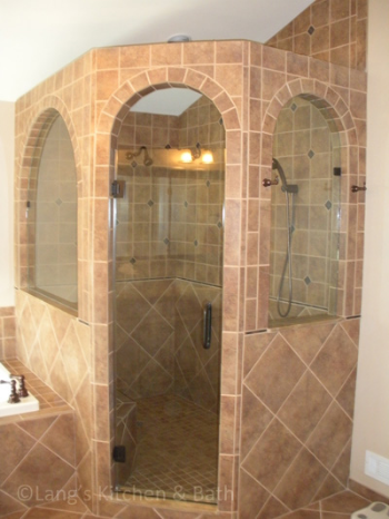 Bathroom design with a customized shower enclosure with an arched doorway.
