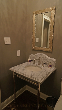 Bathroom design featuring a marble countertop and custom sink legs.
