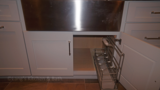 Kitchen cabinet with a pull out accessory for cleaning supplies.