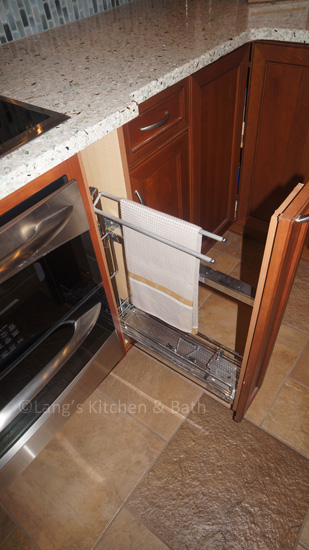 Kitchen design with a pull out accessory for cleaning supplies and towels.