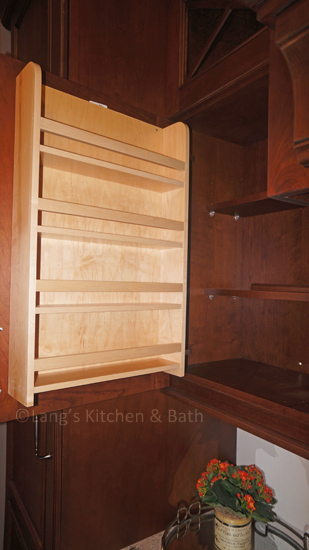 Spice storage shelves attached to the door of a kitchen cabinet.