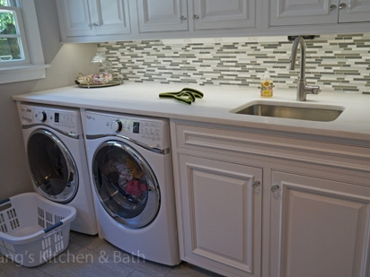 laundry room design with undercounter washer and dryer and laundry sink.